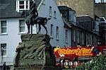 A tour Bus proceeds along Princes Street,the main thoroughfare in Edinburgh beneath the Castle Walls.