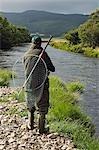 Une pêcheur de saumon pêche à la mouche la glisse Drumlaing sur la rive sud du fleuve Ba sur la succession de Benmore Beat.