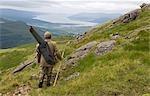 Benmore Estate stalker,Neilson Bissett,on the hill stalking red deer. He carries binoculars,telescope,stalking rifle and walking stick.