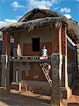 Kinder klettern die Leiter außen auf der obersten Etage eines typischen Doppel-stöckigen Hauses der Betsileo Menschen im südlichen Hochland von Madagaskar.