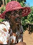 A Malagasy woman wearing a locally made raffia hat.