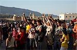 Maroc, Fes. Contre la toile de fond des vieux murs et mosquées de la médina du XIIIe siècle, jeunes femmes voilées et non voilées assistez à un concert gratuit à côté de la Place Boujloud pendant la Fes Festival de musiques sacrées du monde.