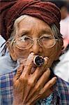 Myanmar. Burma. Nyaung U. An old bespectacled woman smokes a local cheroot in Nyaung U market.