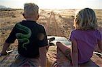 La Namibie, du Damaraland. Avec le plus haut sommet de la montagne du Brandberg Namibie dans les fond deux jeunes enfants jeu de go affichage du haut d'un quatre roues motrices en lumière après-midi tardive.