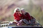 Brandberg Damaraland, Namibie. Deux jeunes enfants assis sur le toit d'un 4x4 jeu affichage vers le bas de la vallée de la rivière Huab recherchant insaisissables éléphants du désert avec une paire de jumelles de go.