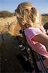 Région de Erongo Damaraland, Namibie. Une jeune fille, ses cheveux soufflant dans le vent, se penche sur le côté d'un véhicule de safari comme il pousse dans des pâturages sur une piste de jeu