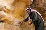 Jordanie, Petra, El Mraibet. Un guide bédouin local fait remarquer certains de la géologie complexe des gisements de grès près de la capitale Nabeatean de Pétra.