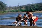 A Samburu moran teaches children the skills of being a warrior during a Cheli & Peacock family mobile safari.