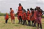 Kenya,Masai Mara National Reserve. A teenage boy on safari dances with the Maasai moran outside a manyatta at the entrance to Masai Mara Reserve.