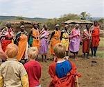 Kenya,Masai Mara National Reserve. Children on a family safari visit a Maasai manyatta or village just outside the reserve.