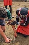 Kenya,Masai Mara National Reserve. A boy on a family safari assists a Maasai warrior as he demonstrates the art of making fire.