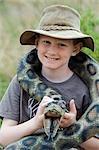 Kenya, Masai Mara National Reserve. Jeune garçon sur safari dans le Masai Mara jouant avec un serpent de jouet.