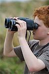 Kenya,Masai Mara National Reserve. Young boy on safari in the Masai Mara looking through binoculars .