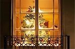 Christmas ornaments on tree behind window