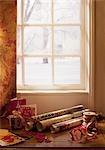 Noël, papier d'emballage, ruban, cadeaux et cartes près de fenêtre