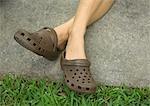 Personne traversant les jambes aux chevilles, porter des chaussures de jardinage