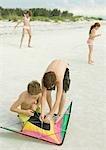 Boys preparing kite on beach