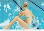 Woman in bikini sitting by pool in transparent chair