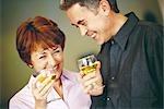 Senior couple holding up glasses of white wine