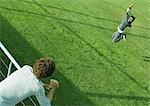 Teenage boy leaning on railing, watching teenage girl jumping on grass