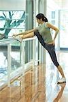Woman stretching leg on barre