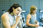 Hommes dans la salle de gym, une face d'essuyage