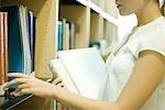 Jeune femme à atteindre pour les livres sur une étagère de bibliothèque, recadrée vue