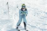Girl skiing down ski slope, full length