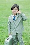 Jeune garçon habillé en costume, brandissant de téléphone portable, mallette de transport
