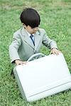 Jeune garçon habillé en costume, accroupi dans l'herbe, ouverture de porte-document