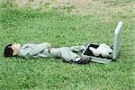 Jeune garçon habillé en costume, couché dans l'herbe à côté de la mallette ouverte contenant des ours en peluche