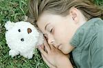 Boy lying in grass with eyes closed, head resting on teddy bear