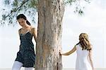 Zwei Schwestern herumlaufen Baumstamm, kleines Mädchen Baum mit der Hand berühren