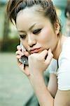 Jeune femme à l'aide d'un téléphone cellulaire, main sous le menton, en regardant vers le bas