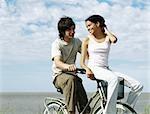 Vélo jeune couple, femme, assise sur le guidon, regarder par-dessus l'épaule