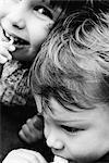Zwei Geschwister Essen Lutscher, Mädchen Lächeln in die Kamera, Nahaufnahme