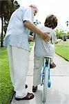 Senior homme aider son petit-fils à apprendre à faire du vélo