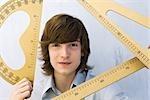 Young man holding various measuring instruments, smiling at camera