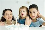 Kleines Mädchen Ausblasen der Kerzen auf der Geburtstagstorte, Mutter und ältere Schwester beobachten
