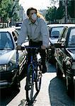 Cycliste dans la circulation dense, avec le masque de la pollution
