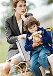 Businesswoman and child sitting, child hugging stuffed dog