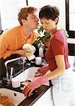 Frau Mann über Theke gelehnt, sie küssen, Abwasch