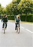 Homme et femme équitation vélos côte à côte, en regardant les uns les autres, pleine longueur, vue de face
