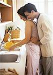 Femme, laver la vaisselle, homme tenant de sa taille et de regarder par-dessus son épaule