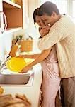 Femme, laver la vaisselle, homme hugging lui par derrière