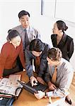 Cinq des associés réunis autour d'ordinateur portable sur la table, la vue grand angle