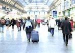 People walking in train station, blurred