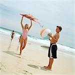 Teenage boy holding beach ball, girl holding kite at the beach