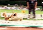 Female long jumper landing in sand pit, blurred motion