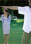 Homme pointant, femme à la recherche en arrière-plan